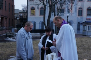 Nina Pooley of St. Bart's, Yarmouth, and David Heald of St. Nick's, Scarborough, prayer with a man in the Old Port.