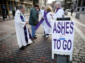 Shirley Bowen offers ashes to a passerby at Monument Square.  Tim Higgins (left) and Peter Bowen look on. (Photo: Robert Bukaty/AP)