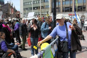 Ann offers a daffodil at the Boston bombing memorial during the procession across Copley Square to Trinity Church.