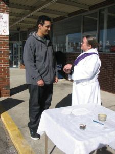 Deacon Wendy Rozene talks with with a young man at Ashes to Go in 2014.