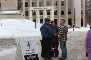 Bishop Lane and Canon Ambler listen to a young man at Monument Square.